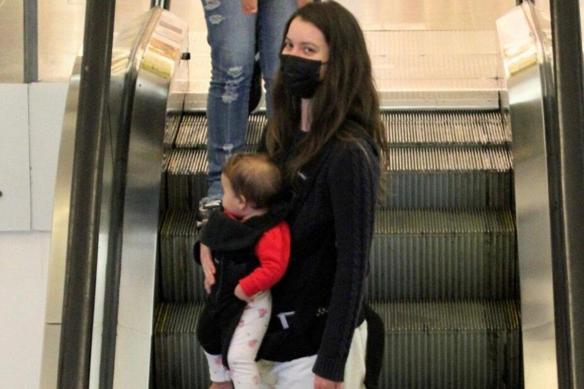 Nathalia Dill com a filha no colo, na escada rolante do shopping
