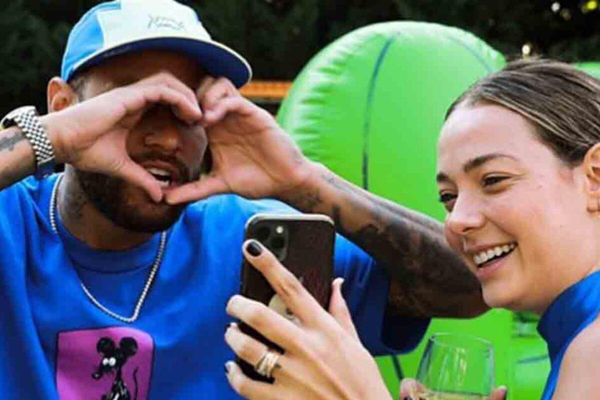 NEymar fazendo coraçãozinho com as mãos diante da ex-Carol Dantas, que tira foto
