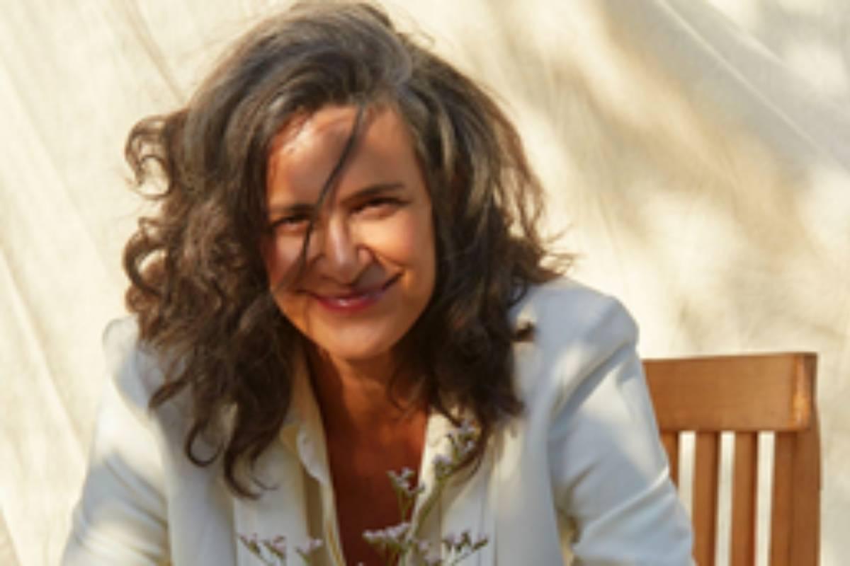 simone de branco sorrindo sentada em uma cadeira com roupa branca