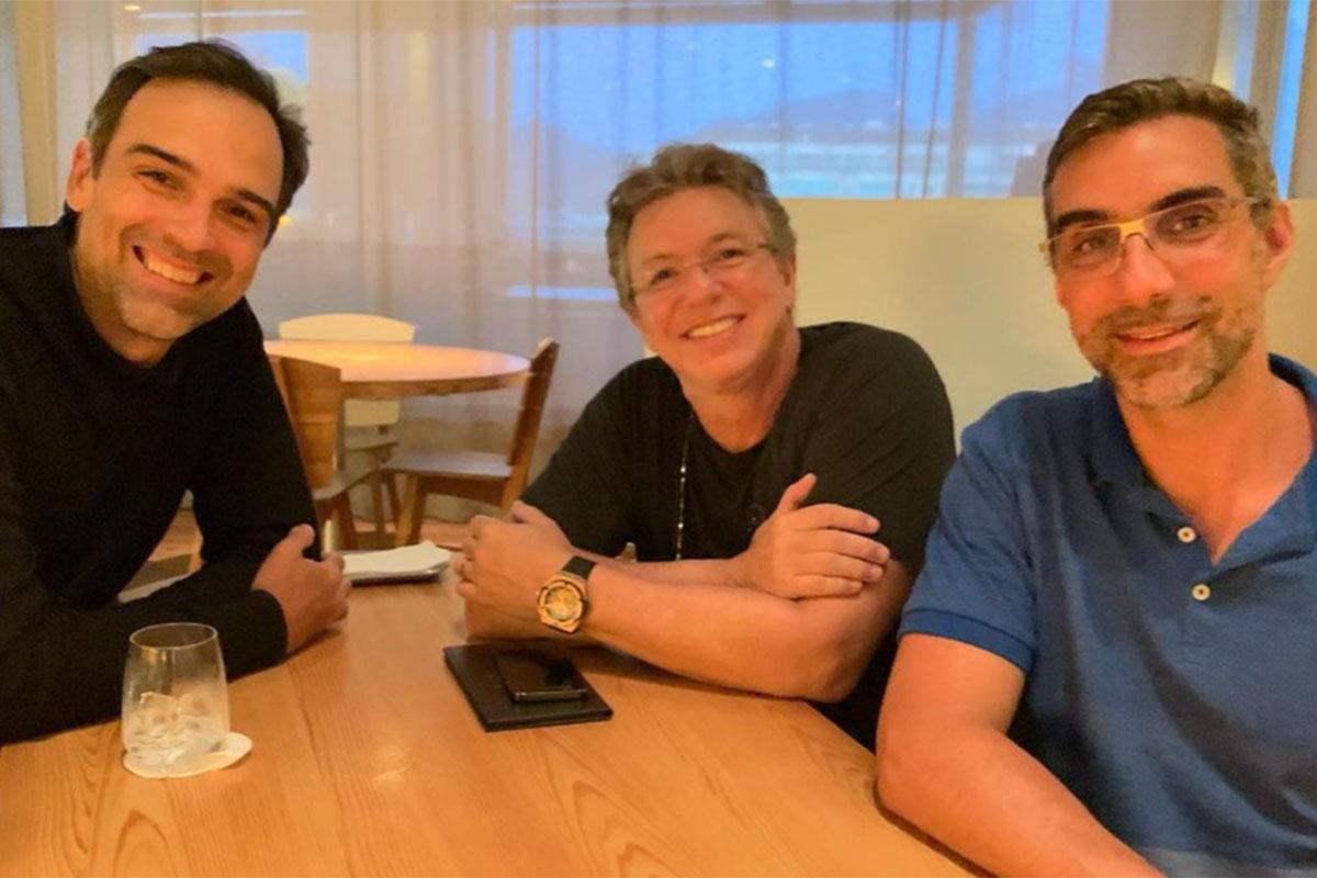 Tadeu Schmidt e Boninho sentados em mesa de restaurante