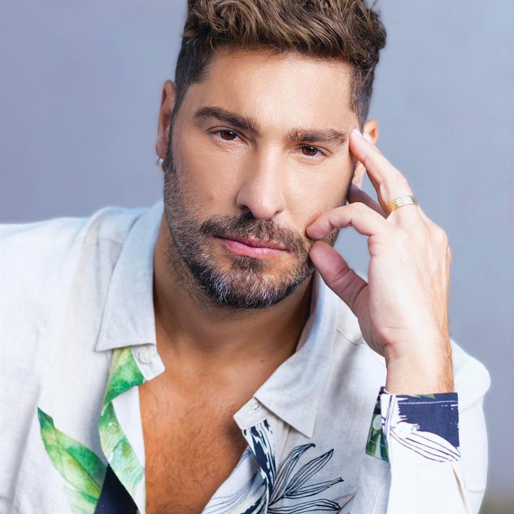 Victor Pecoraro faz pose segurando o rosto